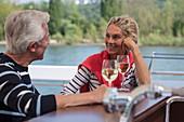 Couple enjoys white wine on sundeck of river cruise ship during a cruise on the Rhine, near Koblenz, Rhineland-Palatinate, Germany, Europe