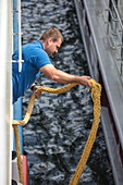 Sailor with rope on board the river cruise ship during a cruise on the Rhine, Koblenz, Rhineland-Palatinate, Germany, Europe
