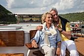 Paar auf Sonnendeck von Flusskreuzfahrtschiff während einer Kreuzfahrt auf dem Rhein, Kamp Bornhofen, Rheinland-Pfalz, Deutschland, Europa
