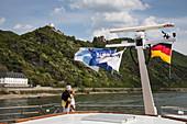 Paar an Deck von Flusskreuzfahrtschiff während einer Kreuzfahrt auf dem Rhein mit Burg Sterrenberg und Burg Liebenstein dahinter, Kamp Bornhofen, Rheinland-Pfalz, Deutschland, Europa