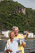Couple makes selfie photo on sundeck of river cruise ship during a cruise on the Rhine, Sankt Goarshausen, Rhineland-Palatinate, Germany, Europe