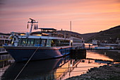 River cruise ship at the pier during a cruise on the Rhine at sunset, Ruedesheim am Rhein, Hesse, Germany, Europe