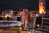 Couple on sundeck of river cruise ship during a cruise on the Rhine at dusk, Ruedesheim am Rhein, Hesse, Germany, Europe