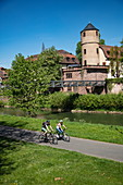 Cyclists on cycle path along the Tauber with the former Princely Court and White Tower of the city wall behind it, Wertheim, Spessart-Mainland, Franconia, Baden-Wuerttemberg, Germany, Europe