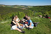 People enjoying a picnic on a slope above the Main, Wertheim, Spessart-Mainland, Franconia, Baden-Wuerttemberg, Germany, Europe
