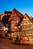 Fountain and half-timbered houses at the historic Schnatterloch market square with Mildenburg Castle at dusk, Miltenberg, Spessart-Mainland, Franconia, Bavaria, Germany, Europe