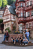 Young people enjoy ice cream while sitting around fountain with half-timbered buildings at the historic Schnatterloch market square, Miltenberg, Spessart-Mainland, Franconia, Bavaria, Germany, Europe