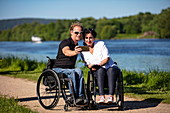 Couple in wheelchairs making selfie photo on the Main, Großwallstadt, Spessart-Mainland, Franconia, Bavaria, Germany, Europe