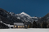 Church chapel in snowy winter landscape in front of mountain panorama at night, Germany, Bavaria, Oberallgäu, Oberstdorf