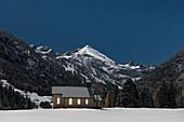 Kapelle in verschneiter Winterlandschaft vor Bergpanorama bei Nacht, Deutschland, Bayern, Oberallgäu, Oberstdorf