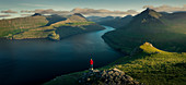 Man with a red jacket at Hvithamar near the town of Gjogv on the Faroe island of Eysturoy with a panoramic view of the fjord