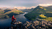 Man sitting at Hvithamar near the town of Gjogv on the Faroe island of Eysturoy with a panoramic view of the fjord