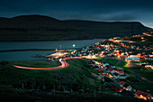 Eidi village on Eysturoy in the Faroe Islands at night with curved road and car lights