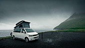 VW camper van with pop-up roof in Gjogv on Eysturoy under rain clouds, Faroe Islands