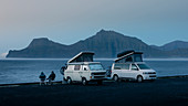 Two white VW camper vans with pop-up roof and people in Gjogv on Eysturoy by the sea, view of Kalsoy Island in the evening, Faroe Islands