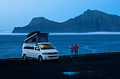 White VW camper van with pop-up roof and couple in Gjogv on Eysturoy by the sea, view of Kalsoy island in the evening, Faroe Islands