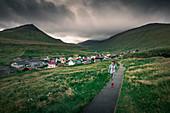 Woman walks on path in front of the village of Gjogv on Eysteroy, Faroe Islands