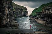 Woman in the gorge in the village of Gjogv on Eysteroy, Faroe Islands