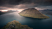 Man at the Klakkur viewpoint near Klaksvik on the island of Bordaoy with a view of Klasoy and Kunoy in sunset, Faroe Islands