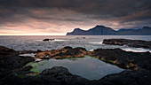 Seaside water pools at Gjogv in sunset with a view of Kalsoy, Faroe Islands