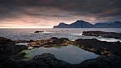 Wasserpools am Meer bei Gjogv im Sonnenuntergang mit Blick auf Kalsoy, Färöer Inseln\n