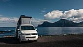 Weißer VW Campingbus mit Aufstelldach in Gjogv auf Eysturoy am Meer, Blick auf Insel Kalsoy bei Sonnenschein, Färöer Inseln\n