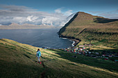 Woman hikes at the village of Gjogv on Eysteroy with gorge, sea and mountains, Faroe Islands