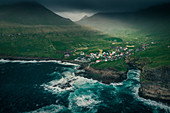 Village Gjogv on Eysteroy with gorge, sea and mountains, from above, Faroe Islands