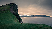 Woman hikes on cliff on Kalsoy Island, Faroe Islands