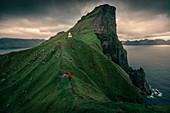 Man hikes to lighthouse on Kalsoy Island, Faroe Islands