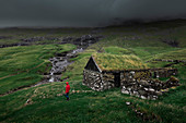 Man in red jacket in front of huts with grass roofs in the village of Saksun on Streymoy Island, Faroe Islands