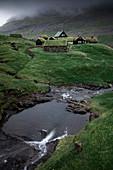 Hütten mit Grasdach und Fluss im Dorf Saksun auf der Insel Streymoy, Färöer Inseln\n