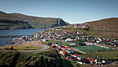 Village of Eidi on Eysturoy in the Faroe Islands by day with curved road