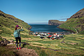 Woman hiking photographs the village of Tjørnuvík on Streymoy on the Faroe Islands by day