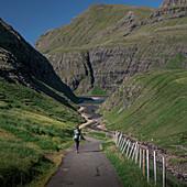 Woman on hiking trail in Saksun Bay, Streymoy, Faroe Islands