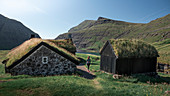 Woman at huts with grass roofs in Saksun village on Streymoy Island, Faroe Islands