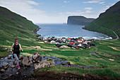 Woman hiking over village Tjørnuvík on Streymoy on Faroe Islands by day