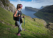 Woman hiking on Streymoy on Faroe Islands by day