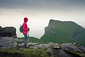Woman hiking in the Streymoy mountains in the rain, Faroe Islands