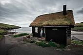 Haus mit Grasdach in der Bucht von Leynar, Färöer Inseln\n