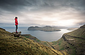 Woman in panorama of Streymoy and Vagar with clouds, Faroe Islands