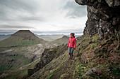 Frau wandert in der Landschaft der Färöer Inseln unter dramatischen Wolken \n