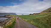 Woman walks on path in the village of Kirkjubøur on Streymoy, Faroe Islands