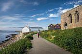 Woman walks to church and ruin in the village of Kirkjubøur on Streymoy, Faroe Islands