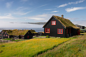 Black houses with red windows and a grass roof in the village of Kirkjubøur on Streymoy in the sun, Faroe Islands