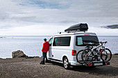 Man next to campervan looking out to sea, Faroe Islands