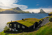 Residential house with a grass roof in the sun in front of the Drangarnier rock formations on Vagar, Faroe Islands