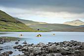 Group kayakers on the Leitisvatn lake in Vagar, Faroe Islands