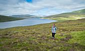 Woman hikes by the Leitisvatn lake near Trælanípa on the island of Vagar, Faroe Islands