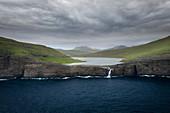 Küste, Wasserfall und Klippen bei Trælanípa auf der Insel Vagar, am See Leitisvatn, Färöer Inseln\n